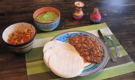 plate of chili con carne, guacamole and tortillas